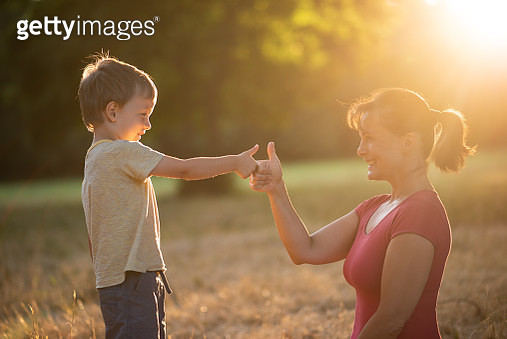 Happy mother and child showing thumbs up to each other - gettyimageskorea