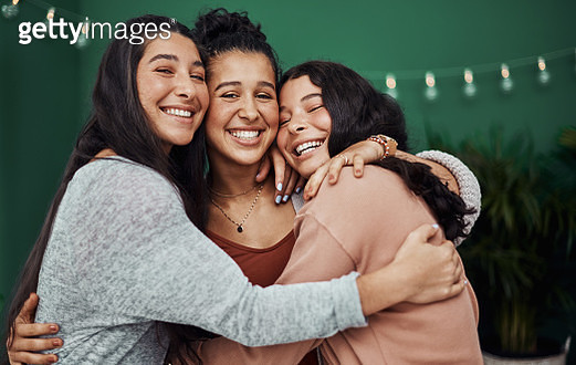 Shot of three happy young sisters embracing at a cafe - gettyimageskorea
