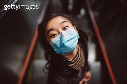 Little girl in medical face mask looking up at camera joyfully on escalator - gettyimageskorea