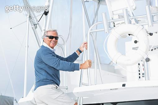 Senior man climbing on his boat, bright sunny day - gettyimageskorea