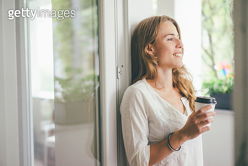 Smiling young woman holding takeaway coffee at the window - gettyimageskorea