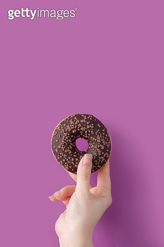 Cropped Hand Of Woman Holding Donut Against Purple Background - gettyimageskorea