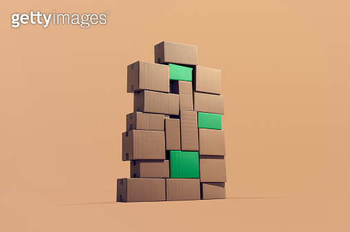 A large pile of cardboard boxes piled on top of each other where three green boxes stands out symbolizing sustainable cargo. - gettyimageskorea