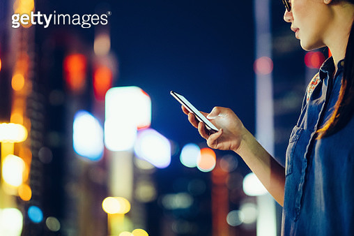 Cropped image of young woman using mobile phone outdoors at night, against city buildings with multi coloured neon lights - gettyimageskorea