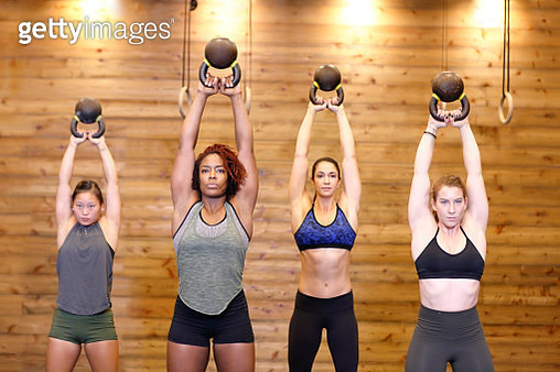 A group of ethnically diverse women working out at the gym holding kettlebells above their head. - gettyimageskorea