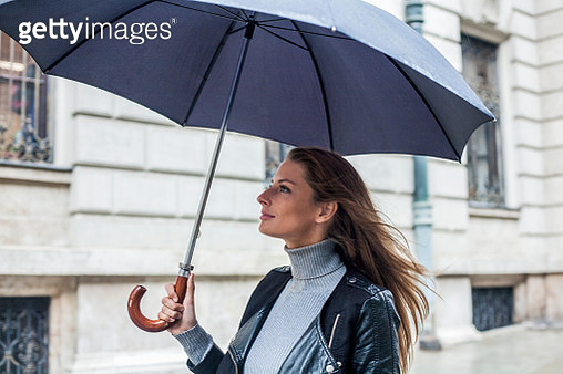 Female commuter on her way to work, holding umbrella, Budapest. - gettyimageskorea