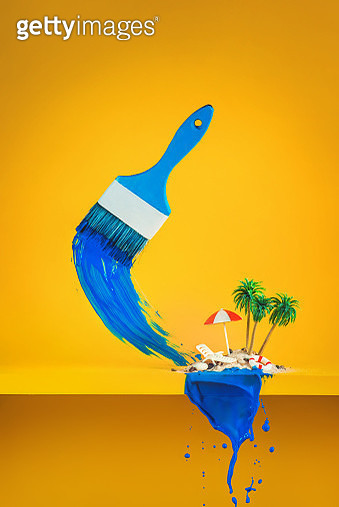 Miniature deck chair with beach umbrella and palm trees on a yellow background with a blue splash of paint. Creative still life - gettyimageskorea