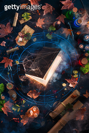 Shining magical book flat lay with spider webs, scrolls, and candles. Occult still life from above - gettyimageskorea