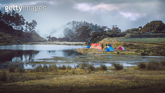 Colorful Tents On Grassy Field By Lake Against Cloudy Sky - gettyimageskorea