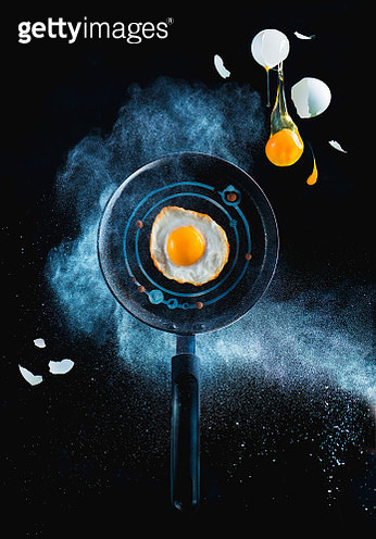 Frying pen with en egg in a cloud of flour and falling yolk on a black bachground. Space breakfast concept - gettyimageskorea