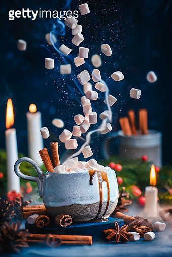 Hot chocolate with flying marshmallows, cinnamon, and anise stars. Hot winter drink, Christmas concept - gettyimageskorea