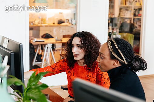 Transgender Woman Working At Computer With Office Colleague - gettyimageskorea