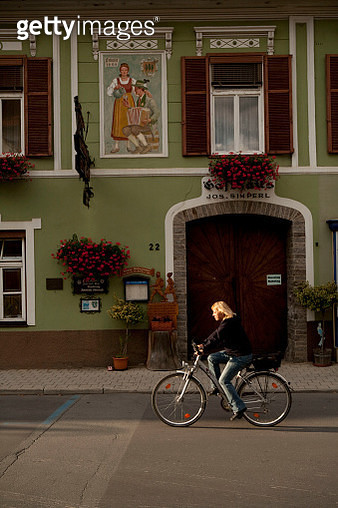 A cyclist rides past a restaurant with mural paintings in Eisenkappel, Austria. - gettyimageskorea