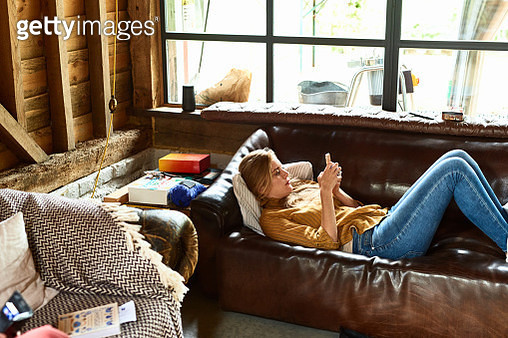 Woman in her 30s relaxing at home on leather couch, texting on phone, social media, messaging, connections - gettyimageskorea