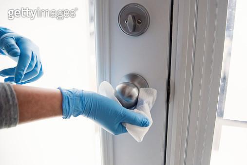 Hands with glove wiping doorknob. - gettyimageskorea