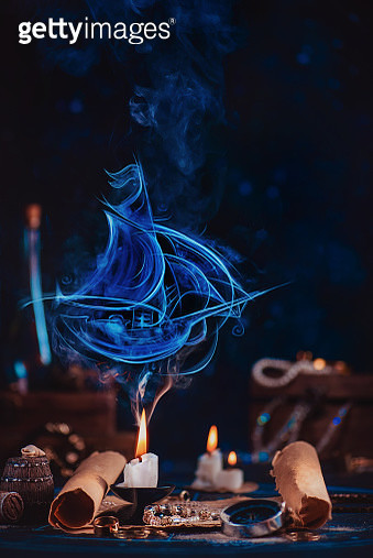 Sailboat silhouette made of smoke above a burning candle in a dark pirate-themed still life - gettyimageskorea