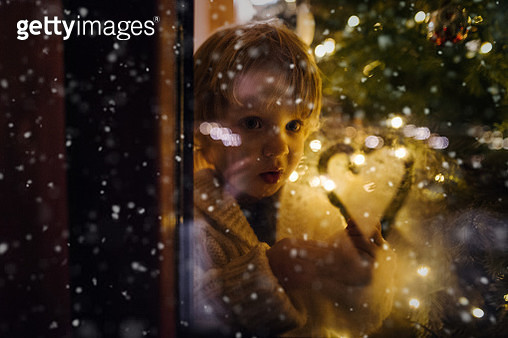 A small cute boy indoors standing by the window at Christmas time, looking out. - gettyimageskorea
