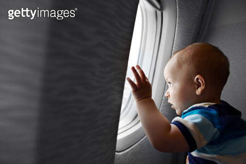 Baby boy looking fascinated out of airplane window - gettyimageskorea