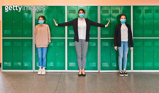 Teenage girls and female teacher wearing N95 face masks standing in front of school lockers. Woman outstretching arms in the distance. High school students at school. - gettyimageskorea