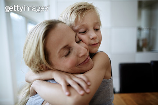 Affectionate mother and son with closed eyes hugging at home - gettyimageskorea