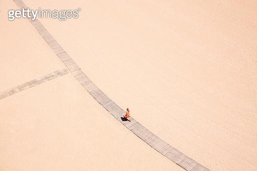 Woman in orange walks along beach boardwalk - gettyimageskorea