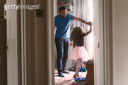 Happy father dancing with daughter in bedroom - gettyimageskorea