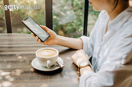 Young woman having a relaxing time in cafe, enjoying coffee while using smartphone - gettyimageskorea