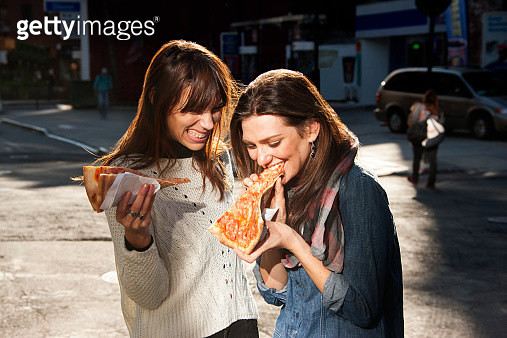 Friends grabbing a slice of pizza on the go - gettyimageskorea
