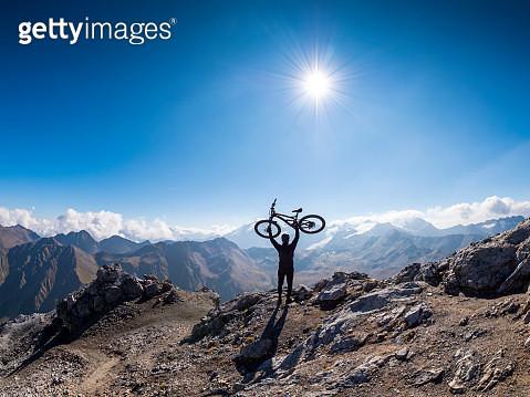 Border region Italy Switzerland, cheering man with mountainbike on peak of Piz Umbrail - gettyimageskorea