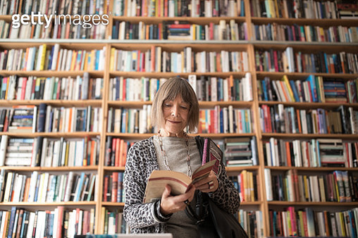 Senior woman reading book while standing against bookshelf - gettyimageskorea