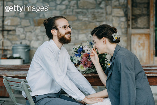 Happy bride and groom sitting at table - gettyimageskorea
