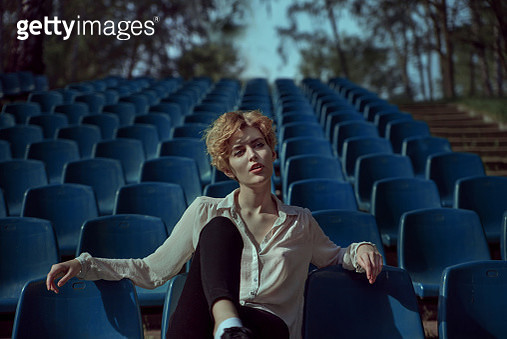 Woman with short hair sitting at blue stadium - gettyimageskorea