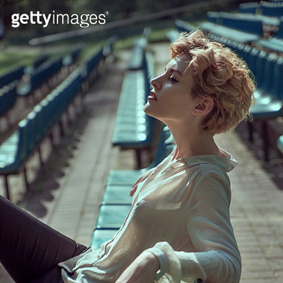 Attractive Female with short hair sitting on blue chairs - gettyimageskorea