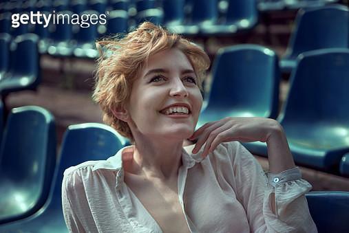 Girl with short hair laughing at stadium tribune - gettyimageskorea