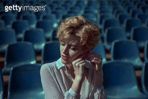 Female with short hair puts on earring - gettyimageskorea
