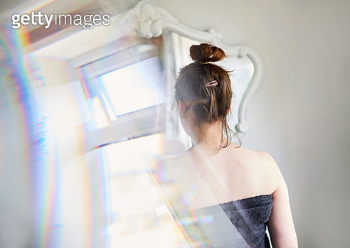 Young Woman looking at her reflection in the mirror - gettyimageskorea