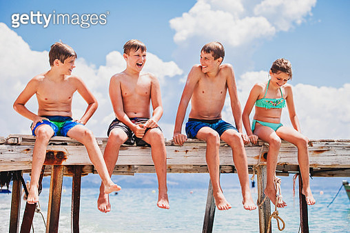 Children on vacation in Greece, sitting on a pier, talking and having fun - gettyimageskorea