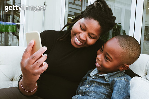 A mother and son using a mobile phone - gettyimageskorea