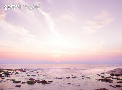 Sunset over sea on rocky beach - gettyimageskorea