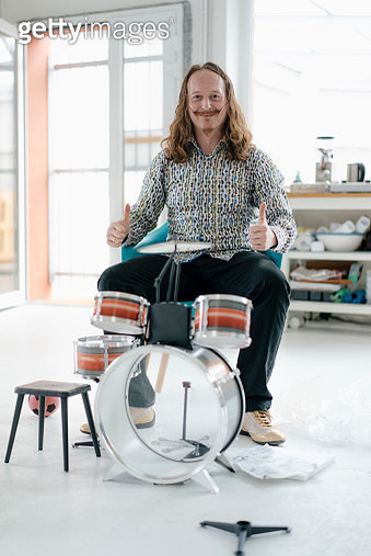 Portrait of confident man sitting at toy drums - gettyimageskorea