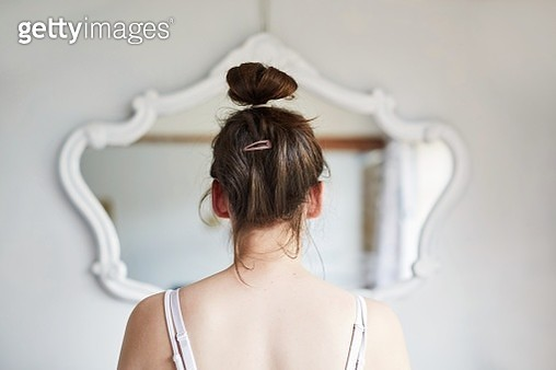 Young woman looking in the mirror - gettyimageskorea