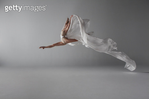 Ballerina performing a grand jeté draped with long white silk, fabric flows behind her beautifully as she jumps through the air - gettyimageskorea