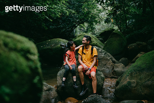 Father and daughter sitting on rock in jungle river, Iriomote Island, Japan - gettyimageskorea