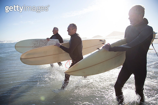 Three senior surfers, aged 55-70,  walking along a sandy beach and preparing to go surfing - gettyimageskorea