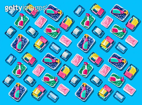 Pattern of cleaning products arranged in rows wrapped in cellophane shot over a blue background - gettyimageskorea