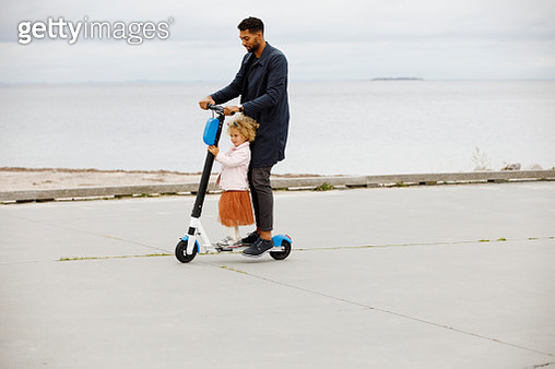 Father and daughter riding together on electric scooter - gettyimageskorea