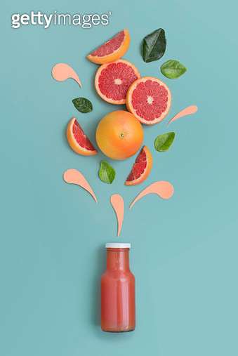 Grapefruits bursting out from a juice bottle. Blue background. - gettyimageskorea
