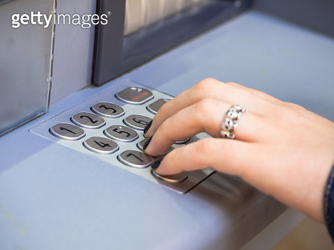 The hand of a woman with fingernails painted black and a ring on a finger on the keyboard of an ATM - gettyimageskorea