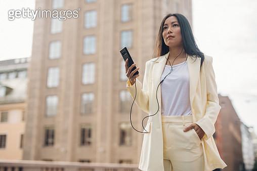 Elegant woman listening to music on the street - gettyimageskorea