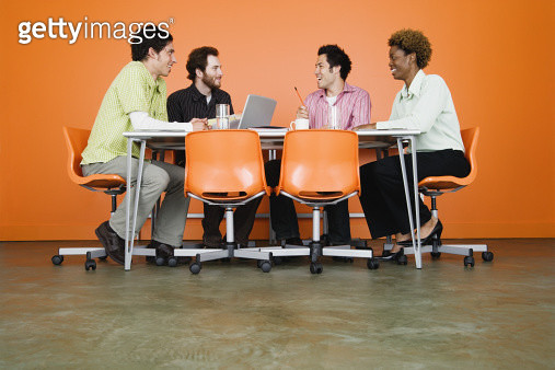 Co-workers at table in conference room, smiling - gettyimageskorea